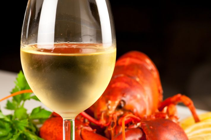 Glass of white wine with cooked lobster